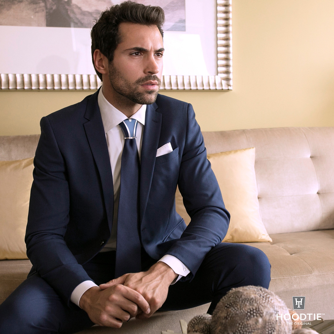 Homme en costume italien bleu cintré, chemise blanche, cravate et bijou de cravate Hoodtie bleu