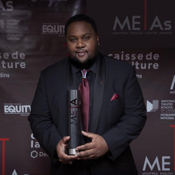 Vêtu d'un total look noir avec cravate et bijou de cravate bordeaux, T. D. Lalla reçoit un Award