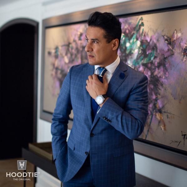 Costume bleu à carreau et accessoire ornant le noeud de cravate en titane bleu