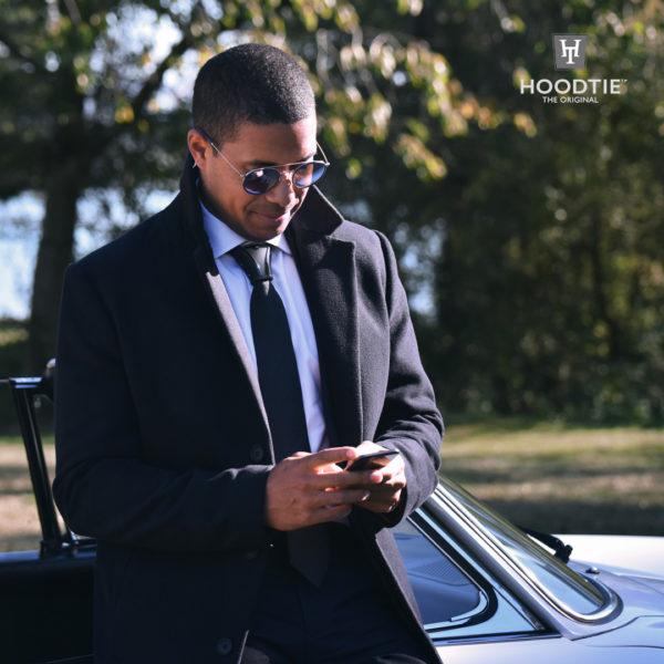 Tenue pour homme stylée avec ce manteau noir et l'accessoire de cravate en titane noir Hoodtie